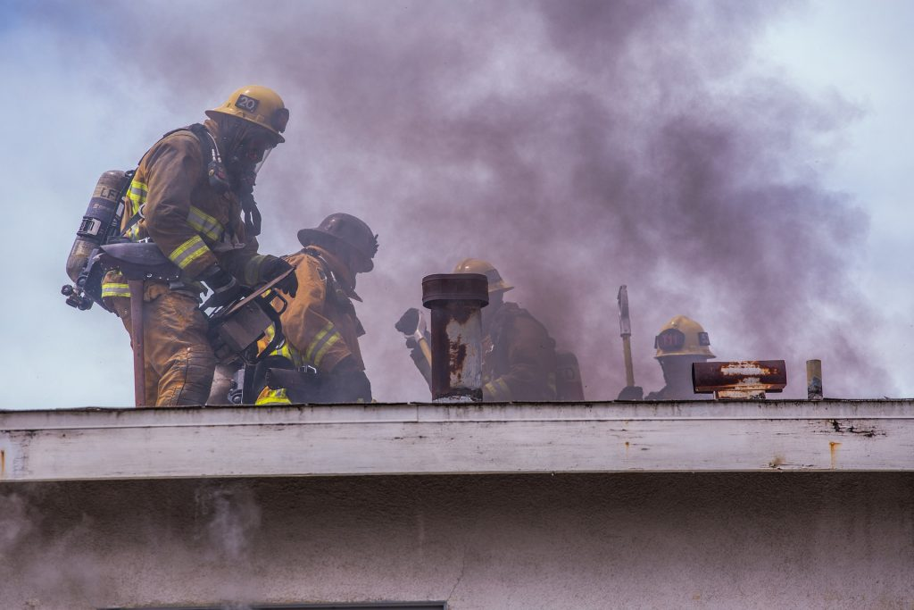 A 4 man fire crew battles fires and smoke from the top of an apartment complex